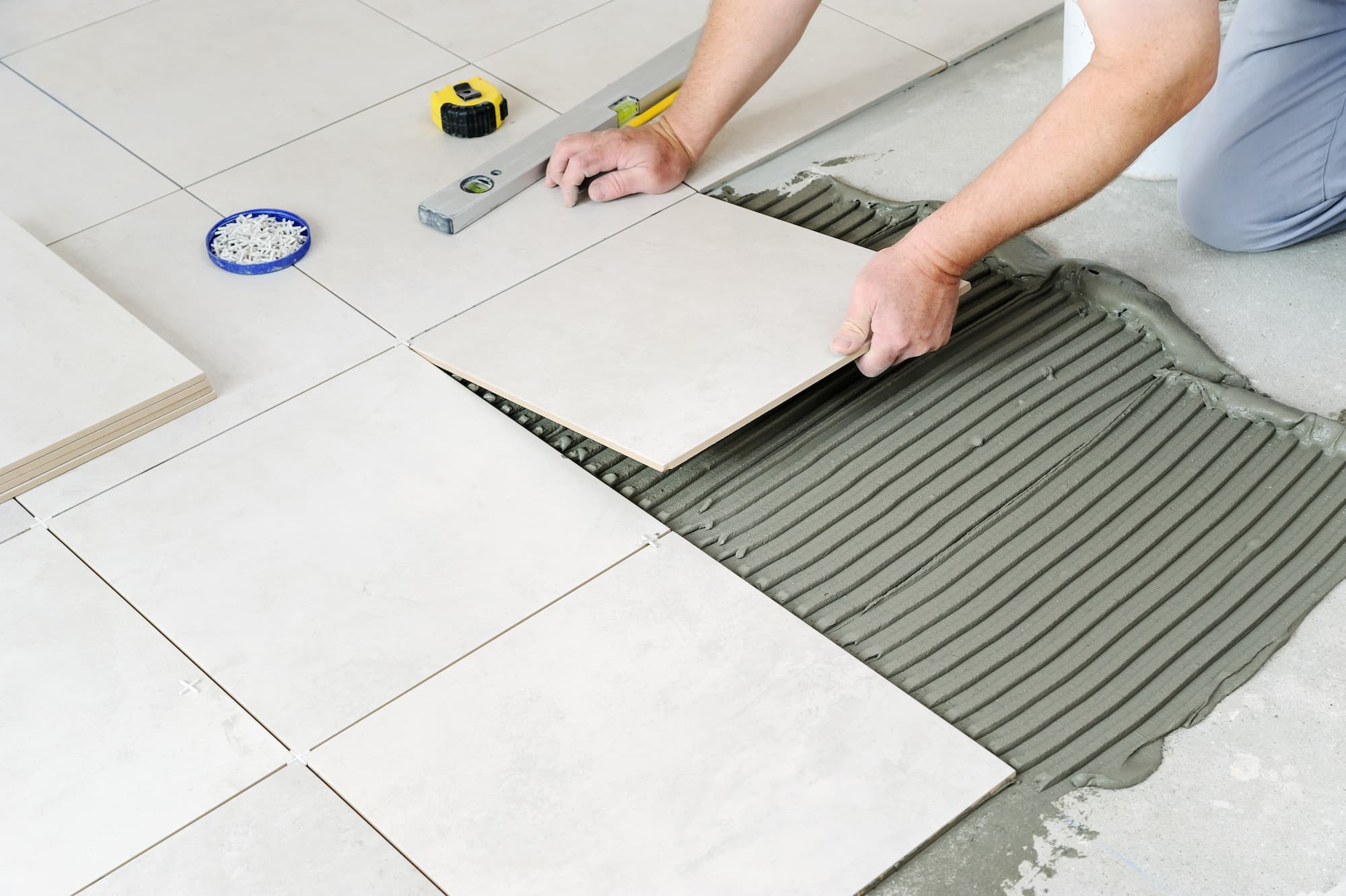 Someone installing tiles into a floor
